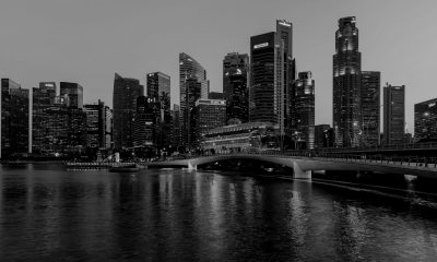 Skyline_of_the_Central_Business_District_of_Singapore_with_Esplanade_Bridge_in_the_evening-scaled-darken