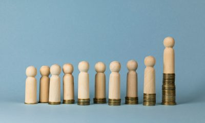 Wooden figures on stacks of coins, concept of wealth and poverty. Rising or falling wages, social inequality.